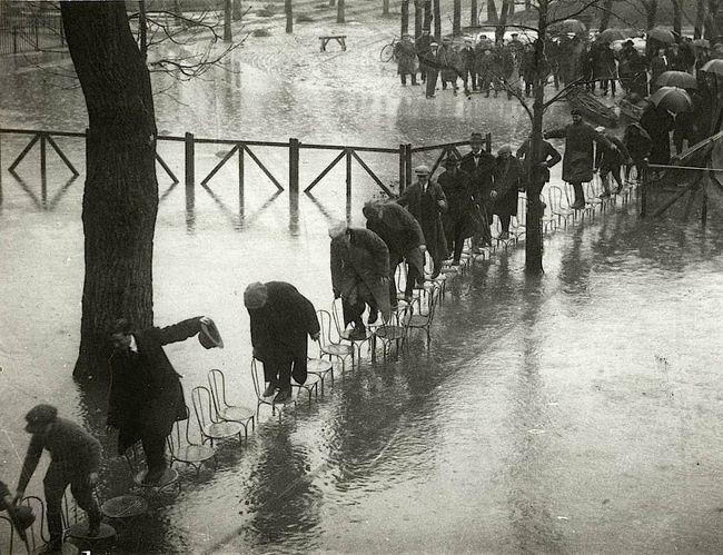 Esta fotografía tomada durante una inundación en Paris en 1924. Las personas improvisaron un puente formado por sillas para cruzar la calle.