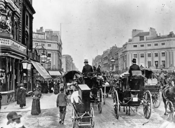 Traffic on Regent Circus, now known as Oxford Circus, London, facing east along Oxford Street. In the foreground is a man towing his barrel organ on wheels, 1888.