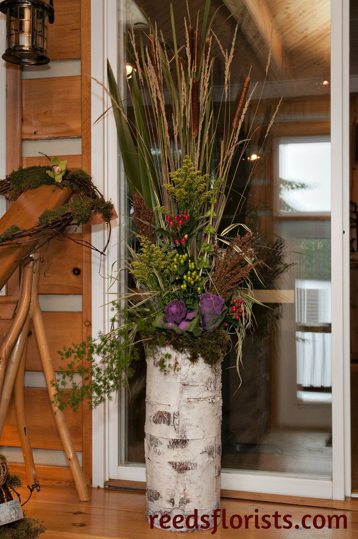 Catails, grasses, ornamental cabbages, broom corn and fern in a birch bark container echo the forest setting of this rustic lodge wedding.