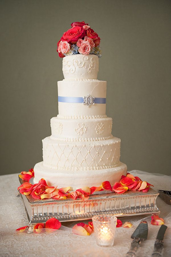 image of a beautiful white five tier round wedding cake decorated with a light blue ribbon and silver brooch and a coral, pink, and blue floral topper - cake is on a silver stand decorated with coral, pink, and yellow rose petals - photo by Houston based wedding photographer Adam Nyholt