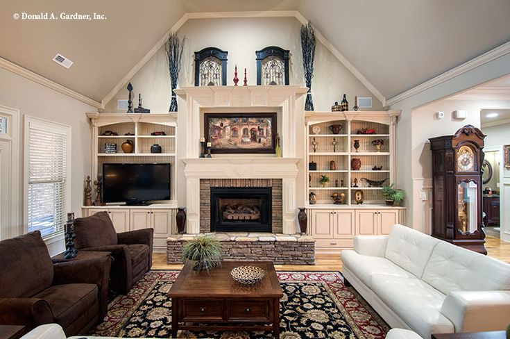 The great room features a vaulted ceiling a fireplace and built in bookshelves the for Built in designs living room