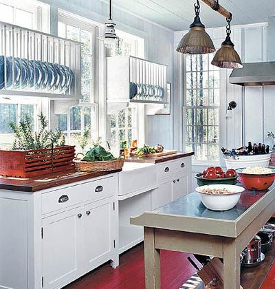 a kitchen with white cabinets and a red floor