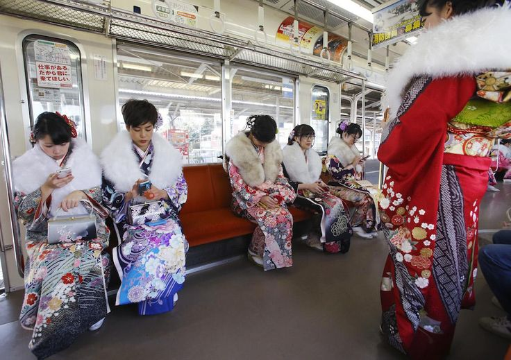 Dressed in Japanese kimonos, a group of Japanese youths who will turn 20 this year, the traditional age of adulthood in Japan, sit in a train after a Coming of Age ceremony at Toshimaen amusement park on the national holiday in Tokyo, Monday, Jan. 11, 2016.