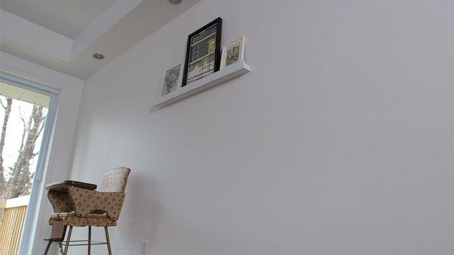 AVANT : La décoration est très minimaliste avec un mur blanc sur lequel est posé une tablette et trois cadres.