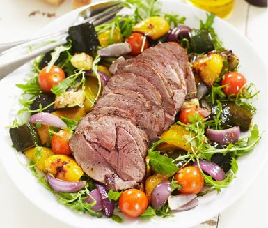Saftig lammstek med ratatouillesallad är en god middag som passar vilken helg på året som helst. Paprika, zucchini, cocktailtomater och ruccola är grönsaker som passar till det rosastekta köttet och en bit bröd.