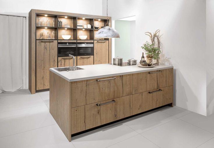 Massief houten keuken met composiet werkbladDeze landelijk keuken is voorzien van een kookeiland met gootsteen, kookplaat en keukenschuiven met horizontale greepjes. Daarnaast zijn er keukenkasten voorzien aan de muur met ingebouwd keukenapparatuur. De massieve deuren stralen vakmanschap uit en zorgen voor enorm veel warmte. De zwarte aflijning tussen de kasten zorgt voor dat tikkeltje extra. De verlichting in de open kasten zorgt voor de warme sfeer in de ruimte. Het witte werkblad in…