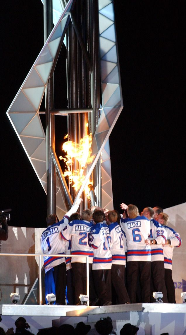 """Members of the """"Miracle on Ice"""" gold-medal winning U.S. hockey team from 1980 light the Olympic cauldron during the Opening Ceremony at Rice-Eccles Stadium."""