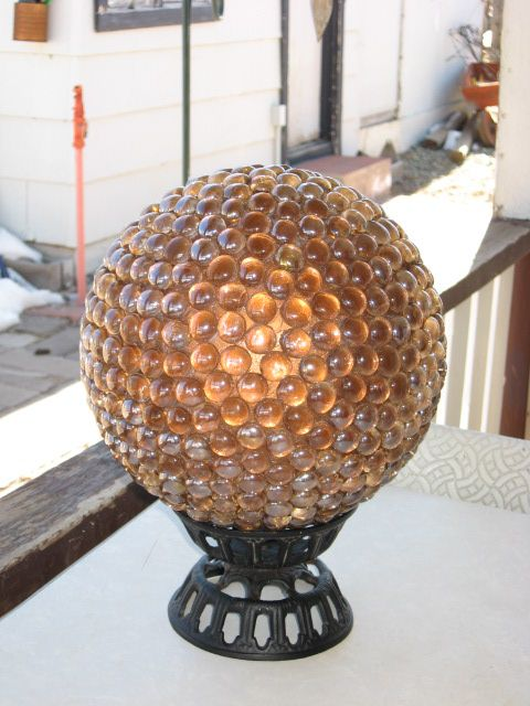 "One of my garden ""gazing"" balls. I made this using an old bowling ball for the base. I spray painted it a copper color and glued on flat marbles using a clear all purpose silicone sealant. It sits in my garden all summer, but I store it in the shed in the winter due to the cold freezing climate I live in."