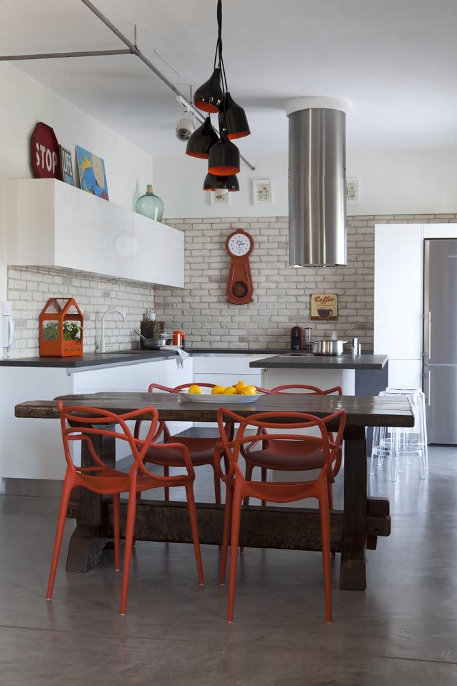 Kitchen and dining room - Masters chair by Philippe Starck + Eugeni Quitllet in a Greek apartment renovated with an industrial touch. Photographer: Mr. Nikos Alexopoulos