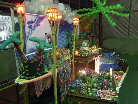 Aluguel+de+decoração+tema+surf,+com+moveis+provençal,+mesa+de+doces+feita+com+prancha+de+surf,+tochas+com+iluminação,+cenario+na+frente+da+mesa+com+areia,+surfista,+perua,+coco+verde,+conchas,+luminarias,+coqueiro+ao+lado+da+mesa+em+malha+tencionada+e+baloes,+onda+de+balões+no+fundo+da+mesa,+bolo+cenografico.+Ótimo+tema+para+quem+não+quer+mais+personagens.
