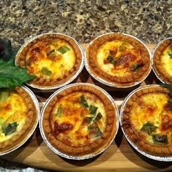 Small tart shells are filled with bacon, Swiss cheese, and green onions creating a hearty mini quiche for brunches or dinner parties.