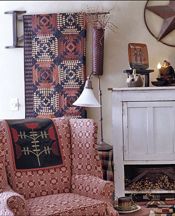 Beautiful Pineapple Log Cabin Quilt folded & displayed on the wall; small quilt over the chair back