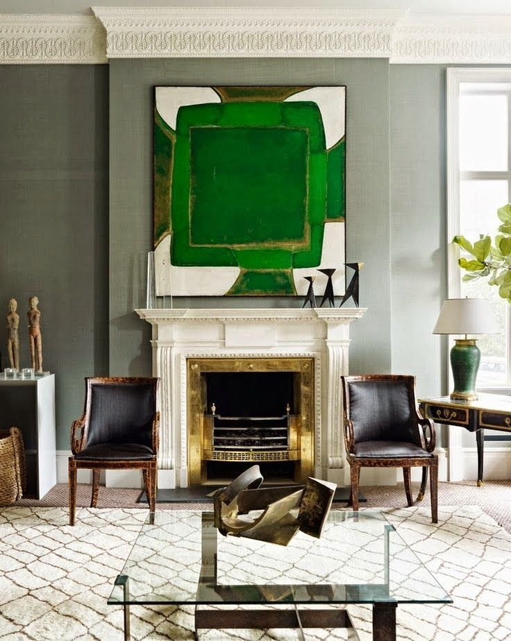 green artwork, brass fireplace surround, gray walls, glass coffee table