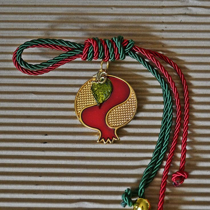 Μπρούτζινο ρόδι δίχρωμο. Διάτρητο χρυσό και κόκκινο με σμάλτο, σε δίχρωμο κορδόνι με μεταλλικά στοιχεία.
