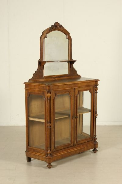 Vetrinetta Umbertina scantonata, fianchi e ante con vetri. Montanti con colonne tornite. Alzata con specchio e ripiano.