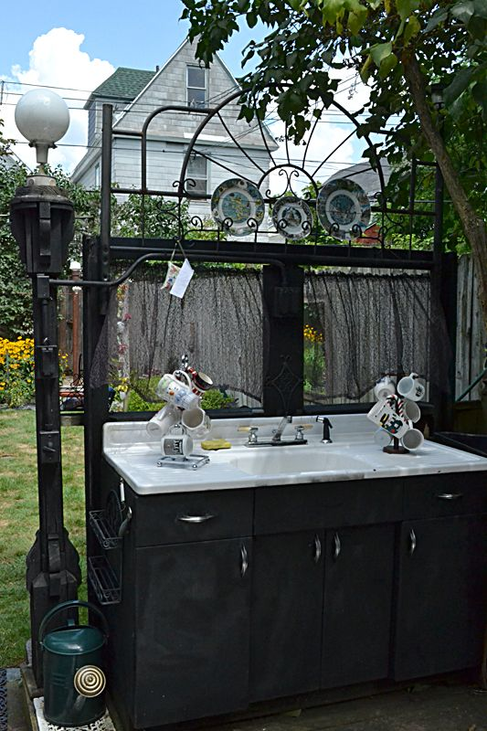 a garden hose supplies the water to this sink on the deck at the home of