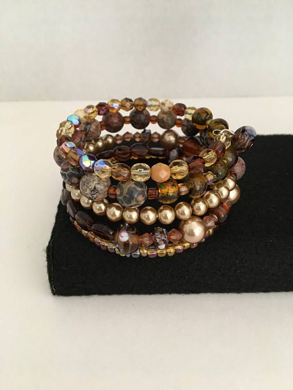 The perfect colors found in nature on a bracelet...this stunning amber, gold and brown wrapped bracelet is made with stainless steel memory wire and is adorned with a fancy bead at each end. All beads are coordinated in the brown hues. The bracelet consists of a mix of glass beads,