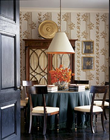The dining room has a light blue ceiling, a favorite Hadley hue for the upper plane. The American Empire mahogany armoire is topped by a Tibetan gong. Next to them are two works on paper by Connecticut artist Mark Sciarillo, also a metalworker, who made the sculpted bronze base of the living room's coffee table. The vellum lampshade, the Eyelet gold-on-ivory wallpaper, and the chairs are all Hadley's designs.