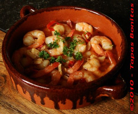 "Prawns in Garlic Sauce - ""Gambas al Ajillo"": Here, we make prawns in garlic oil, in garlic butter or in garlic sauce, using several different recipes but this particular recipe for prawns in garlic sauce is our favorite by far. The secret of this Spanish tapas recipe is in the spicy stock that we extract from the prawn skins and legs that are left over after peeling. We add this stock to the prawns after frying and we let it simmer with the oil for a while to form a powerful prawns garlic…"