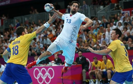 France's Nikola Karabatic, center, leaps in the air to score past Sweden's Tobias Karlsson, left, and Sweden's Kim Andersson, right, during the men's handball gold medal match at the 2012 Summer Olympics, Sunday, Aug. 12, 2012, in London. (AP Photo/Petr David Josek)