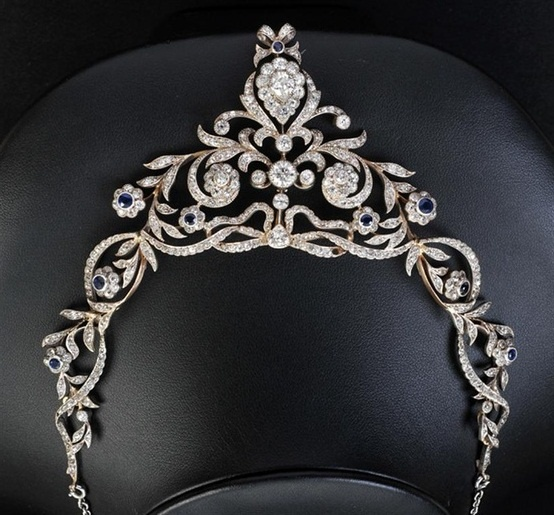 A Diamond and Sapphire Necklace with associated tiara adaptor, the openwork ribbon and foliate scrolls millegrain-set numerous old and rose-cut diamonds with central pear-cut stone suspending knife-edge and collet-set circular-cut diamonds above principle pear-cut diamond, approx 6.5mm x 5.5mm within frame of smaller old-cut stones interspersed with nine round mixed-cut sapphires all set in white metal with yellow reverse framework, tests as silver and 9ct gold in blue leather case.