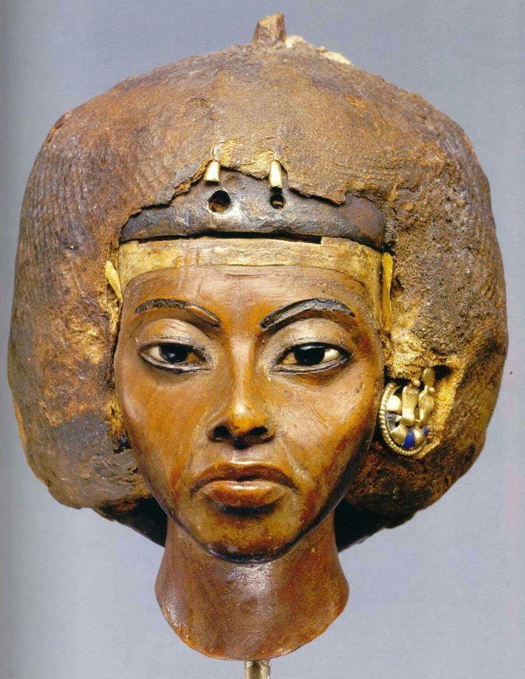 Tiye is de moedr van Achnaton. Dit beeldje van taxushout is maar 3,75 cm hoog. De ogen zijn van albast en ivoor. De lippen zijn rood geverfd en de oorbellen zijn van goud en lapis lazuli. Het haar is van gips en linnen met kralen en was oorspronkelijk getooid met een  zilveren hoofddeksel.