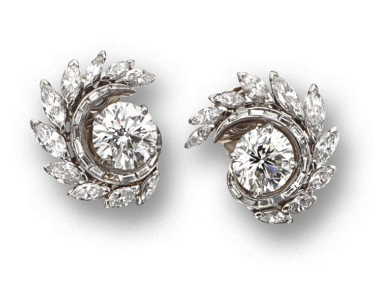 PAIR OF DIAMOND EARCLIPS, CIRCA 1950.  Centering 2 round diamonds weighing 3.26 and 3.37 carats respectively, bordered by foliate swirls set with 20 marquise-shaped diamonds weighing approximately 5.70 carats and 26 baguette diamonds weighing approximately .50 carat, mounted in platinum