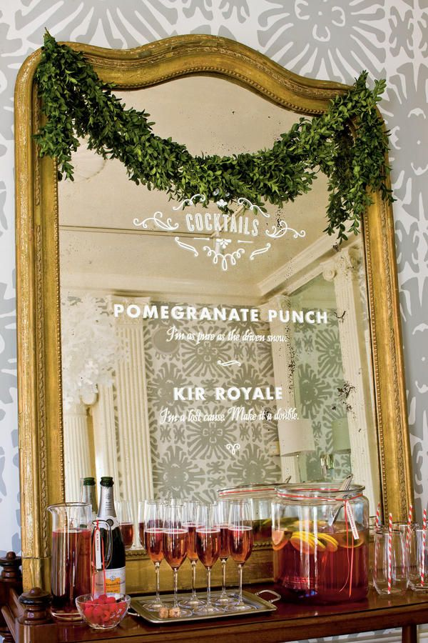 """Unexpected Bar Menu - """"Naughty or Nice"""" Christmas Cocktail Party - Southernliving. Drawing their inspiration from humble chalkboard menus, Gatsby applied a lettered decal to an antique mirror for an elegant bar menu. The letters were easily removed after the party to restore the mirror to its original condition."""