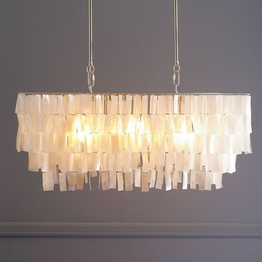 "Lighting. Large Rectangle Hanging Capiz Chandelier - White | West Elm Tiers of shimmering natural capiz shells—often referred to as ""glass oysters"" because of their fragile, translucent appearance—are hand cut and hand strung by talented Filipino artisans to create this piece, which casts a beautifully luminous glow over a dining table.  30.5""w x 14.75""d x 15.5""h. 3 60 watt bulbs. Polished Nickel metal frame."
