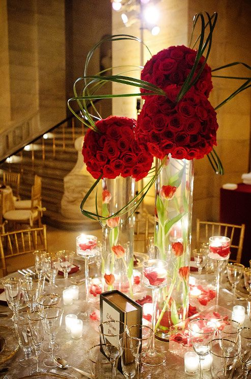Tall glass cylinders are topped with pomanders of red roses and bear grass used architecturally.