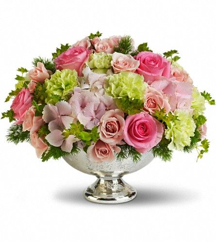 """Teleflora's Garden Rhapsody Centerpiece: this stylish mix of pinks and greens. Presented in a classic Mercury Glass Vase, it's where trendy meets traditional!  Pink hydrangea, light pink and pink roses, green carnations, ming fern and bupleurum are artfully arranged in a Mercury Glass Bowl.  Approximately 13"""" W x 10 1/4"""" H.  * Inspiration for reception flowers."""