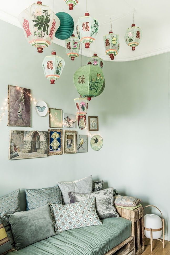 Minty green room with casual sofa - Mixed pattern pillows - Paper lanterns