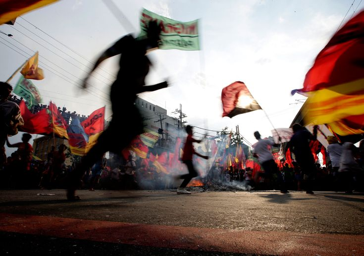 Workers from the militant labor organization Kliusang Mayo Uno (May 1st Movement) dance around a burning effigy of Philippine President Benigno Aquino III to mark the Labor Day celebrations on May 1 near the Presidential Palace in Manila, Philippines. (Bullit Marquez/Associated Press)