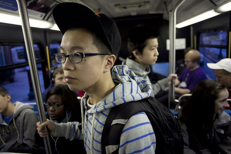 Johnny Huynh (foreground) and his brother, George, ride the bus every weekday to Boston Latin School.