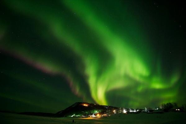 An aurora borealis swirls in the sky over the Yukon River village of Ruby, Alaska