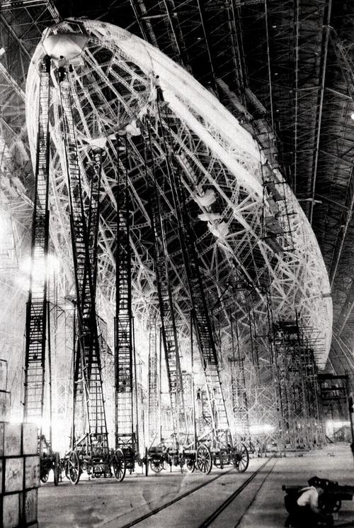 Zeppelins under construction: Men atop giant fire ladders work on airship