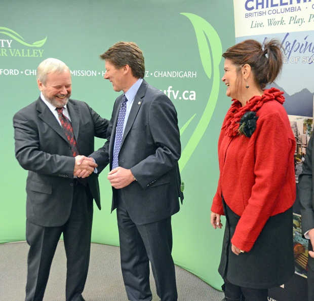 Mayor Sharon Gaetz watches as UFV president Mark Evered shakes hands with BMO vice-president Henry Donkers at a press conference downtown Chilliwack on Friday. BMO has donated the $850,000 building to the university.