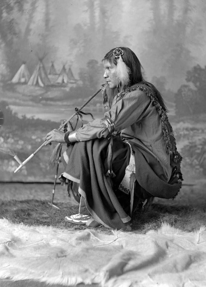 Full length studio profile of unidentified Native American male, possibly Dakota or Arapahoe, squatting and smoking a peace pipe, in front of painted backdrop. - Barry - 1880s