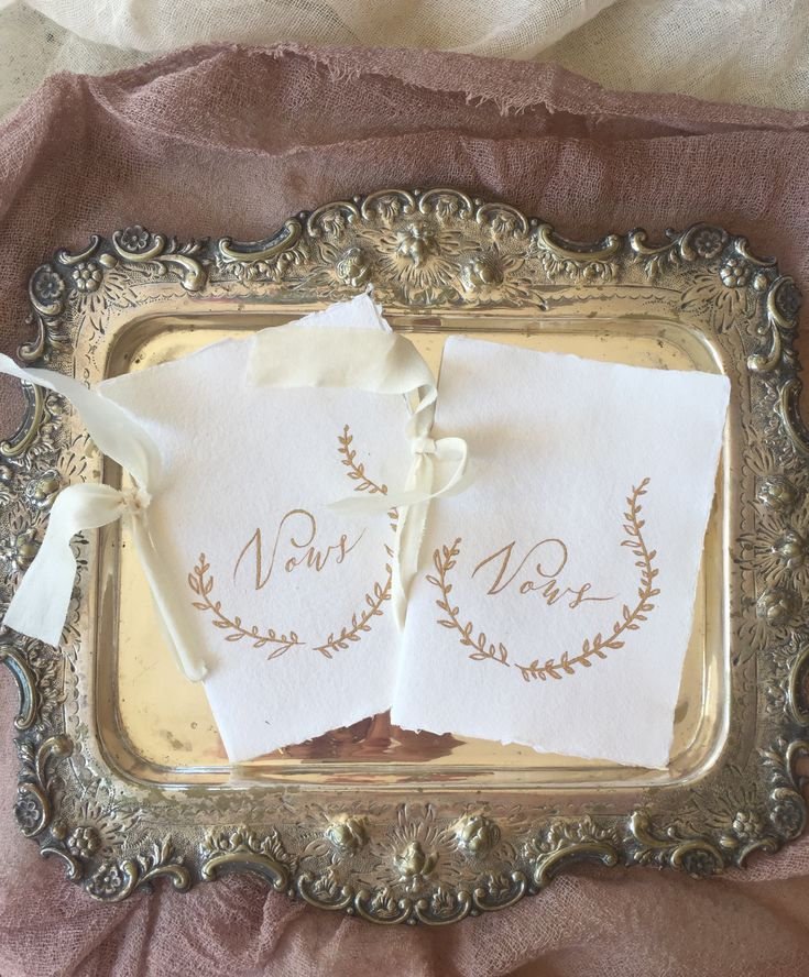 Beautiful handwritten gold ink calligraphy and leaf motif on handmade paper finished with a silk ribbon.