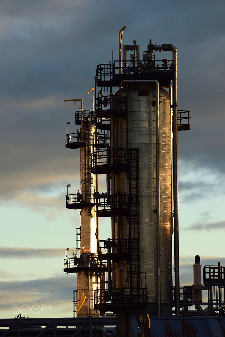 Industrial Age - Chimneys of a petroleum refinery at dusk.