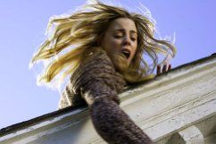 MELISSA GEORGE tries to save her daughter from falling off the roof in THE AMITYVILLE HORROR.