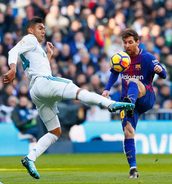 Casemiro of Real Madrid challenges Lionel Messi of Barcelona during the La Liga match between Real Madrid and Barcelona at Estadio Santiago Bernabeu on December 23, 2017 in Madrid, Spain.