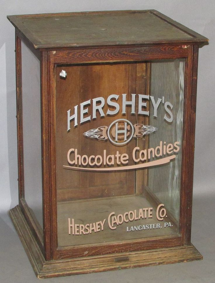 "444.Hershey's Chocolate display case ca. 1870-1910; oak case with three glass sides and a hinged door on the rear having the front glass labeled ""HERSHEY'S Chocolate Candies, Hershey Chocolate Co., LANCASTER, PA"" in silver and brown paint with a painted logo later addition and original finish on wood, 24 ¼""x 24 ¼""x 32 ¼""; Estimate $200.00-$400.00 SOLD FOR: 650.00"