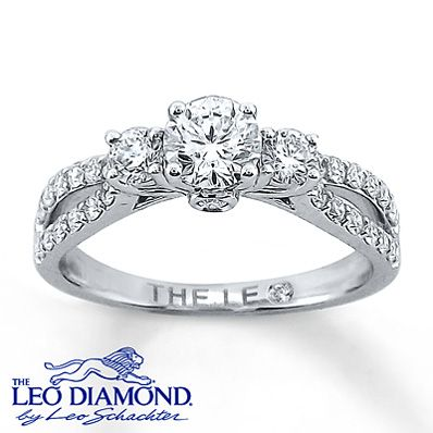 This enticing engagement ring is full of gorgeous Leo diamonds: 1 bigger Leo diamond in the center surrounded by two more Leo diamonds on the side, totaling 1 carat in all. The band, made of beautiful 14k white gold, is embedded with even more small Leo diamonds and splits apart below the center diamonds.