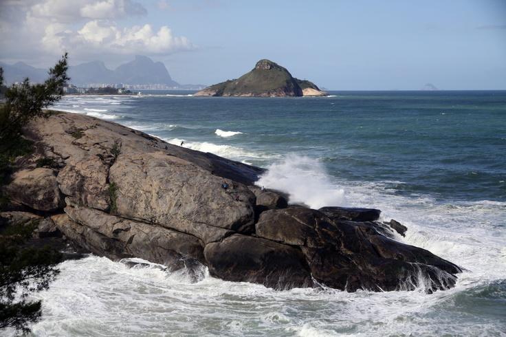 Pescadores na pedra que fica ao lado da estrada que liga o Recreio dos Bandeirantes à Prainha, com o Pontal Tim Maia ao fundo. Rio de Janeiro.