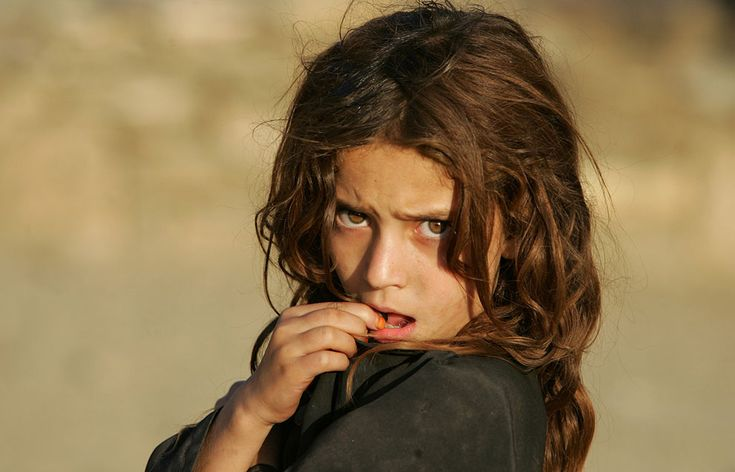 A girl looks at U.S. soldiers of the 1st Battalion, 32nd Regiment of the 10th Mountain Division as they walk by on a patrol near Camp Florida in eastern Afghanistan, on September 7, 2006. (Credit: Saurabh Das/AP)