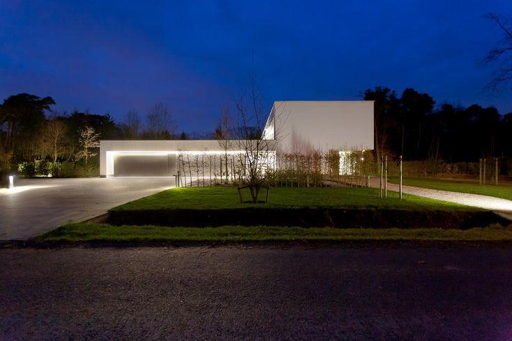 warm witte architecturale woning met een ledlijn verlichting aan voorgevel