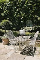 A pair of delicate metal garden chairs flanks a table with a Dutch bird house on the paved patio