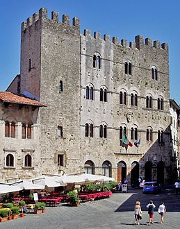 An imposing four-storey stone building with battlements and rows of paired windows, facing onto a town square.
