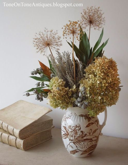 A bouquet of dried limelight hydrangeas, alliums, eucalyptus silver bell pods, artemisia, and grevillea leaves in a favorite brown-and-white transferware pitcher.